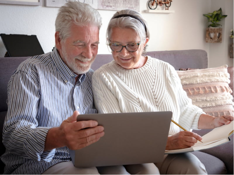 A senior couple looks at the laptop