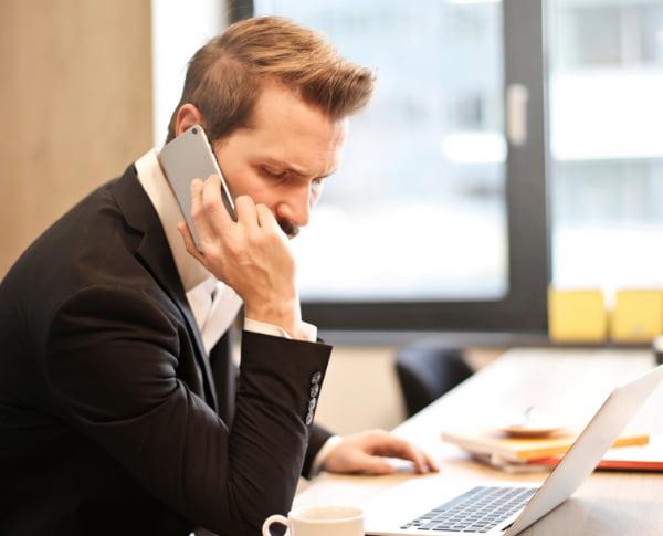 Man using his laptop while talking thru phone