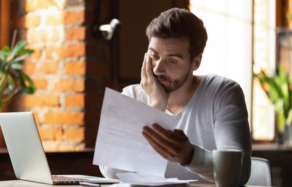 Confused frustrated young man reading letter in cafe
