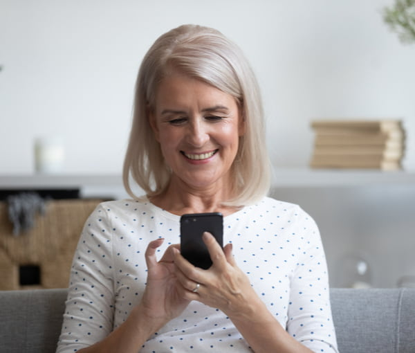 Smiling mature woman holding phone