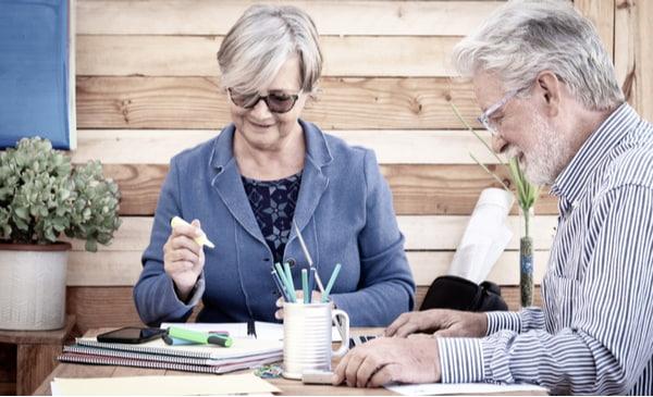 retired senior couple share the same office