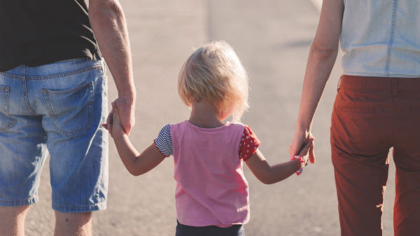 A little girl holding hands of her parents