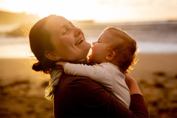Woman happily hugging the baby on the beach